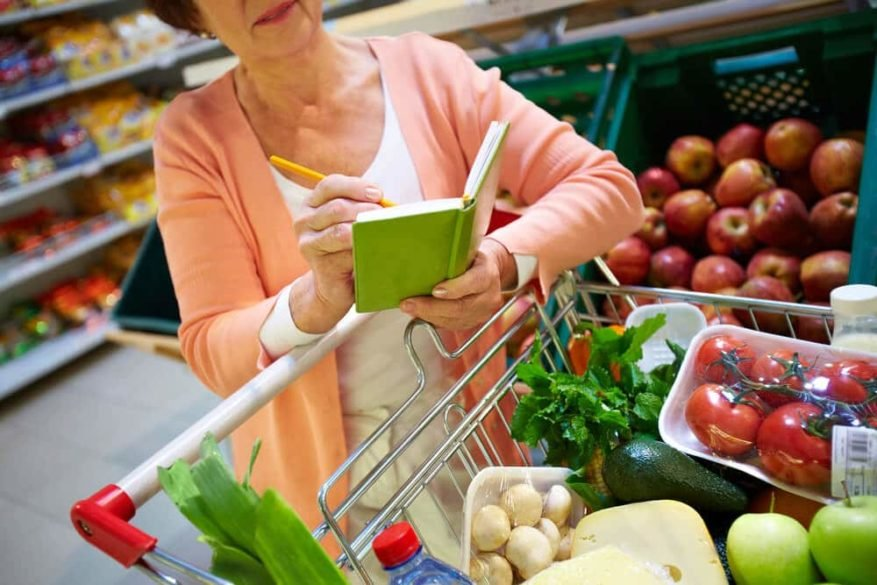 senior woman grocery shopping with a list