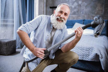 senior man holding a vacuum