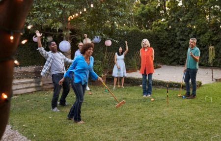 senior friends playing croquet in the back yard