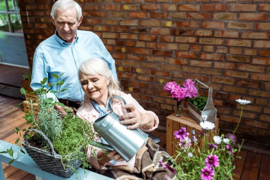 senior couple watering plants on porch