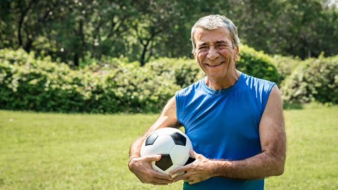 senior man with a soccer ball in his hand