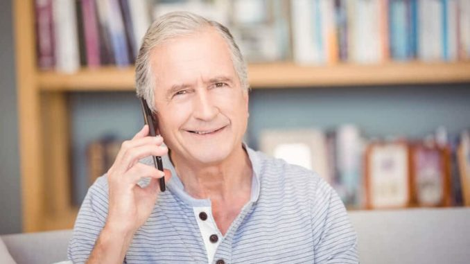 senior man with dementia talking on a cell phone