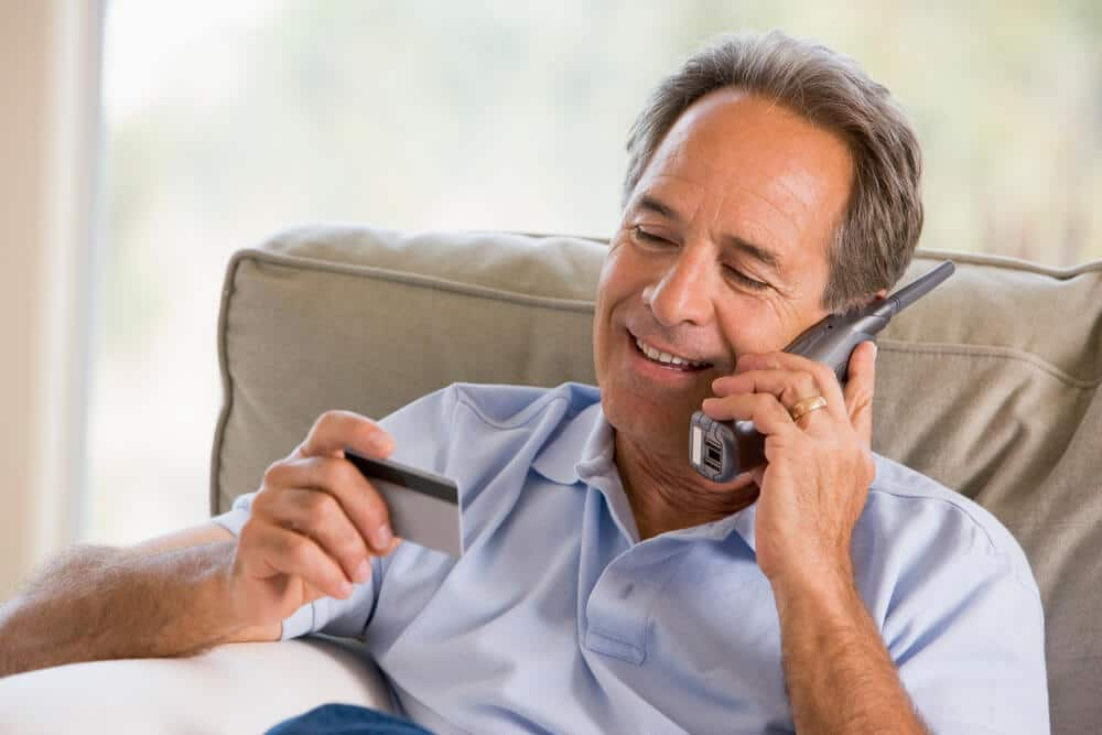 senior man using a large button cordless phone