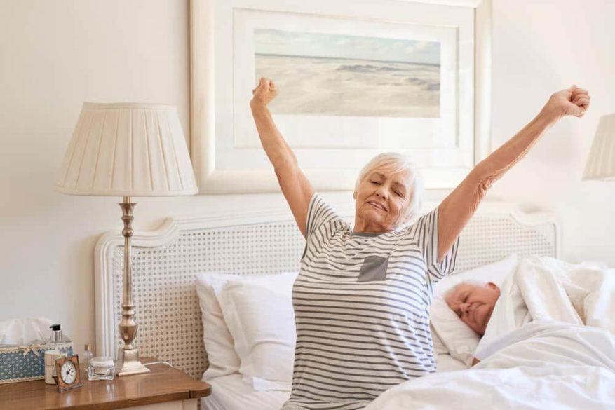 elderly woman getting out of bed with comfortable mattress topper
