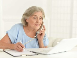 senior woman working on laptop and phone