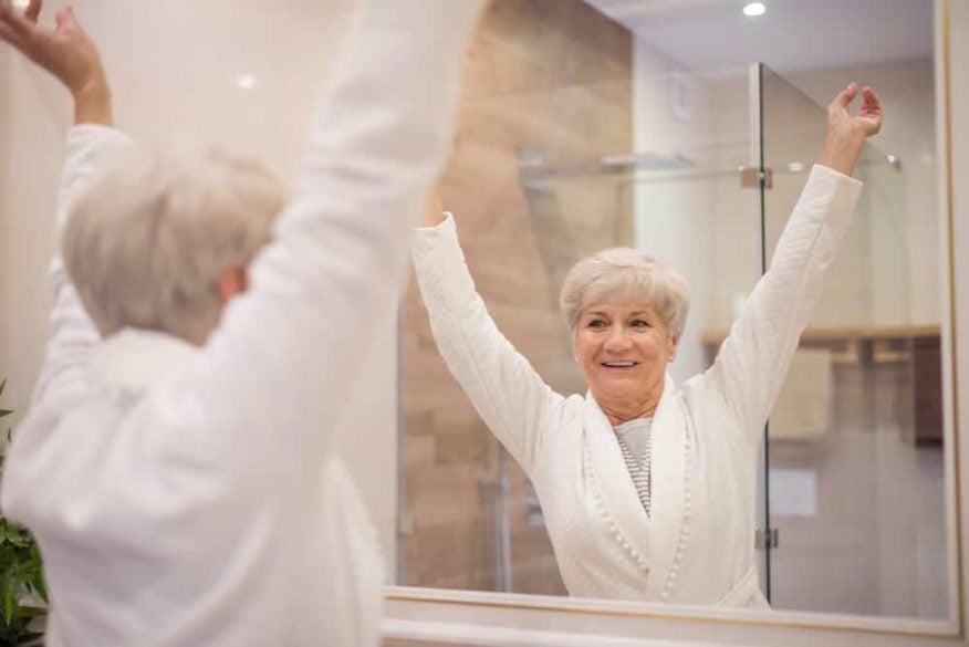 senior woman looking in bathroom mirror