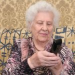 senior woman dialing a simple cordless phone