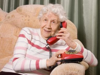 elderly woman using a simple telephone sitting on a couch