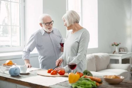 woman chopping up soft foods for elderly man
