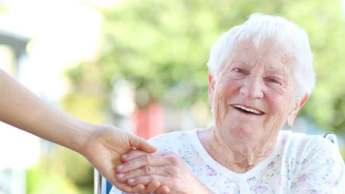 elderly woman sitting in chair with alarm