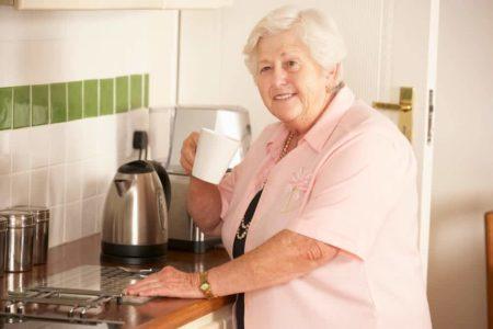 elderly woman smiling while making tea