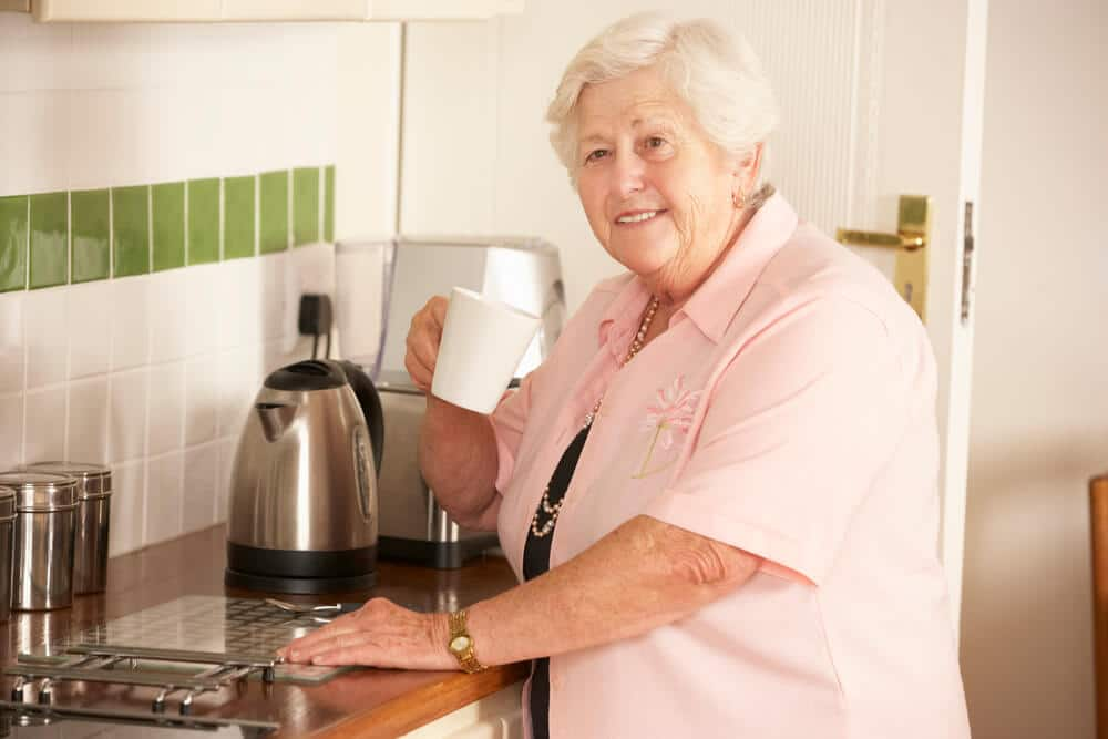 elderly woman smiling while making tea