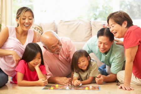 grandparents playing board game with grandchildren