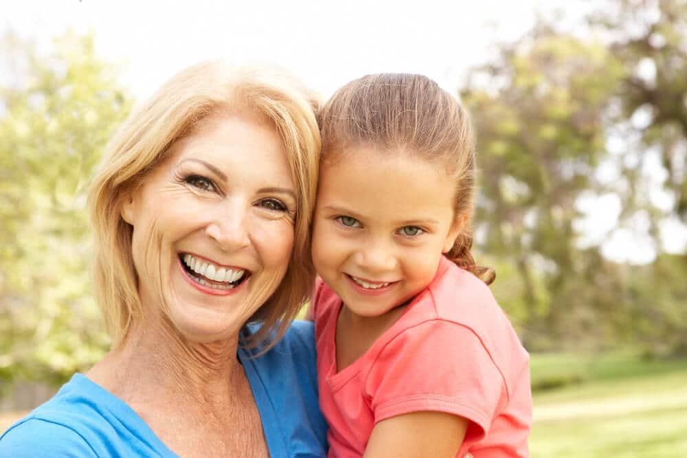 grandma smiling while holding her grandaughter