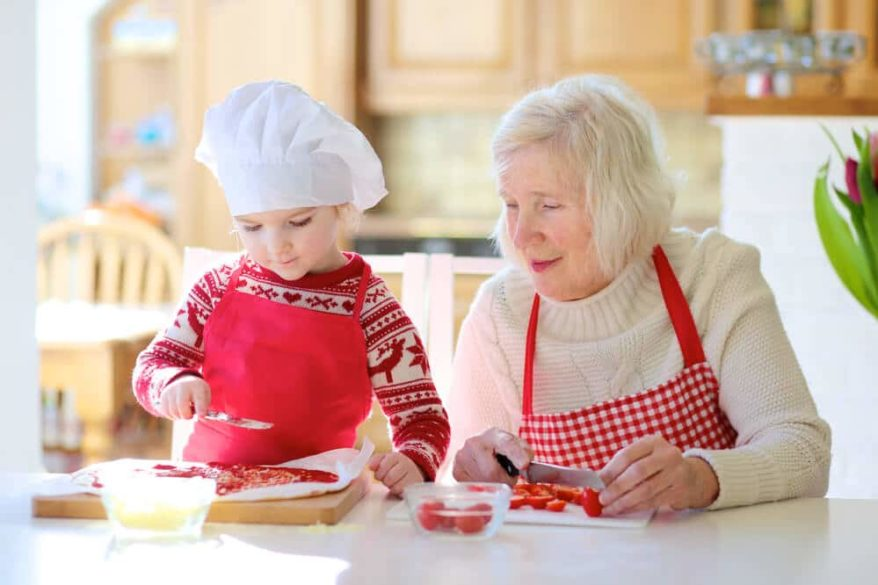 grandmother making a pizza with her granddaughter