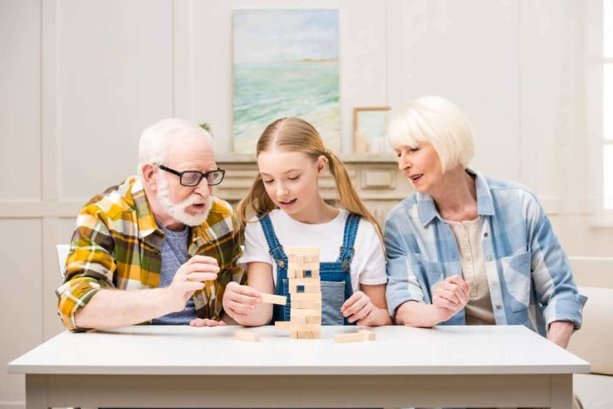 grandparents playing game with teenage granddaughter