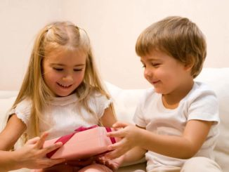 grandkids opening up inexpensive gifts with smiles