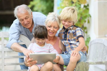 seniors playing with grandkids on tablet