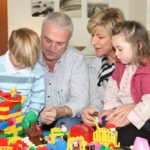 grandfather and grandma playing with toys with their grandkids