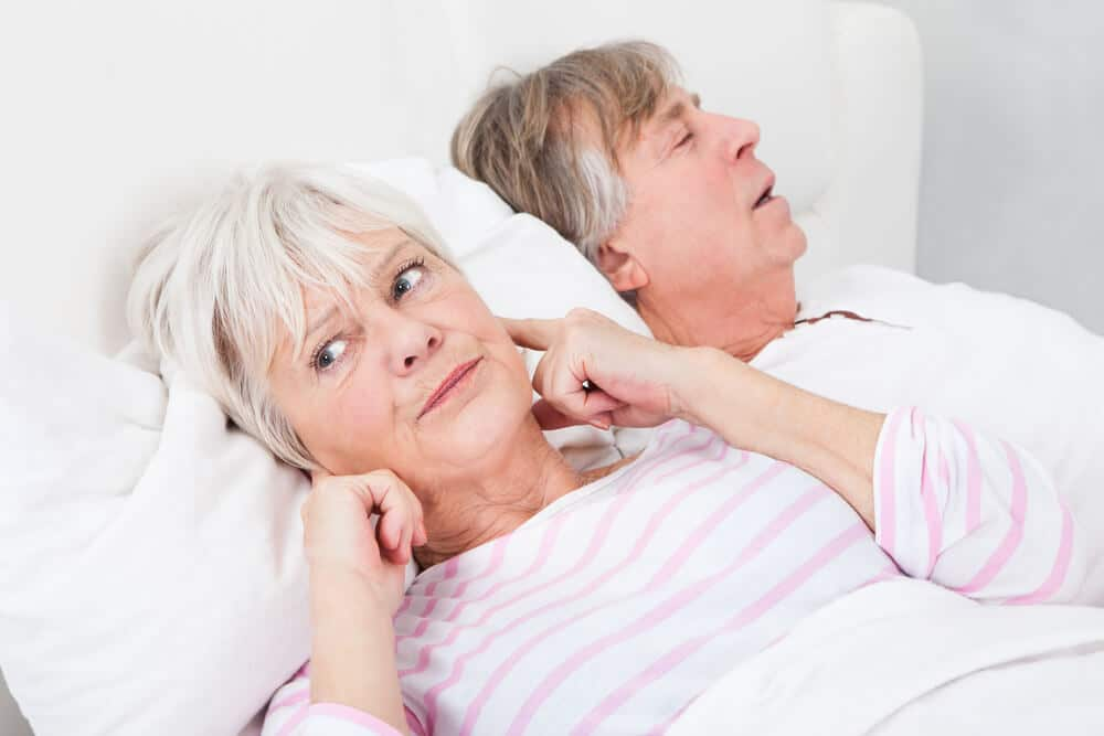 woman plugging her ears because husband snores from sleep apnea