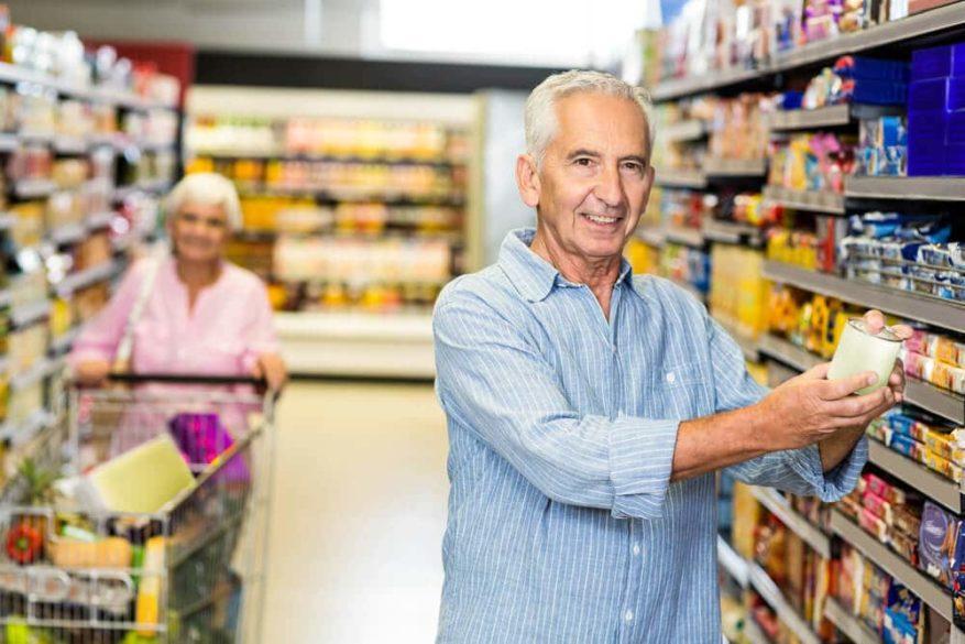 senior man looking at cans of food