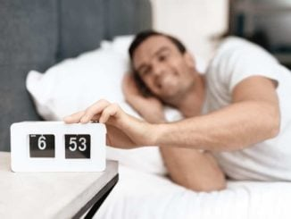 senior man turning off alarm on his clock radio