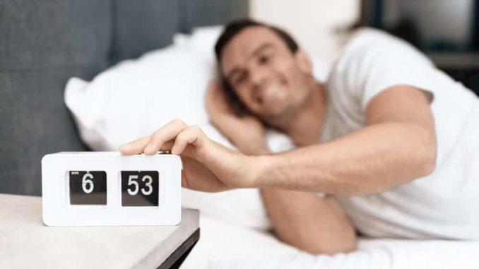 senior man turning off alarm on his clock radio