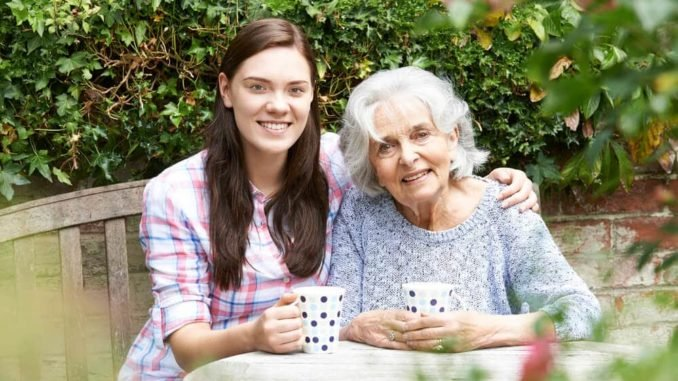 senior with arthritic hands drinking coffee with granddaughter