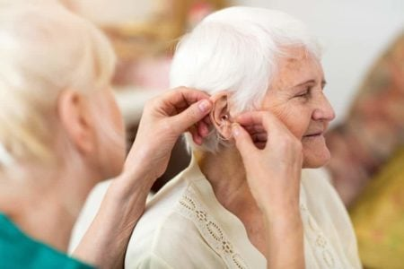 woman helping senior use a hearing aid to deal with her hearing loss