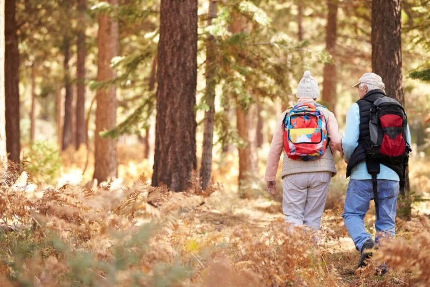 senior man and woman hiking in the woods