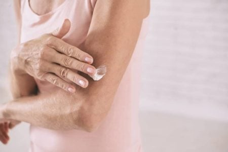 senior woman applying body lotion to her mature skin