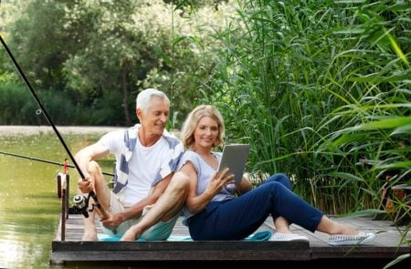 senior couple fishing and reading as their outdoor hobby