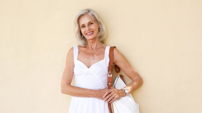 smiling senior woman standing with a purse on her shoulder