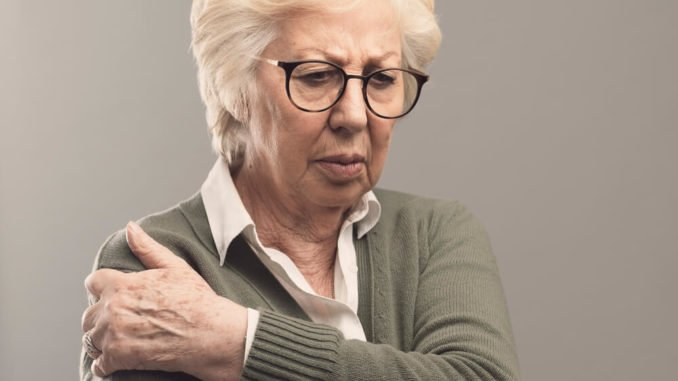 senior woman with arthritis pain from purse