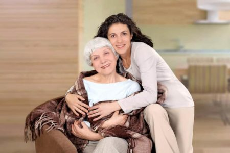woman encouraging her senior mother to go for a walk