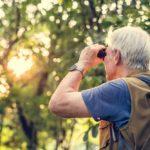 senior man birdwatching with pair of binoculars