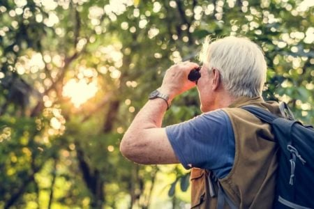 senior man birdwatching with pair of binoculars