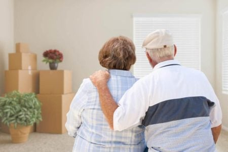downsizing senior couple looking at moving boxes in their home