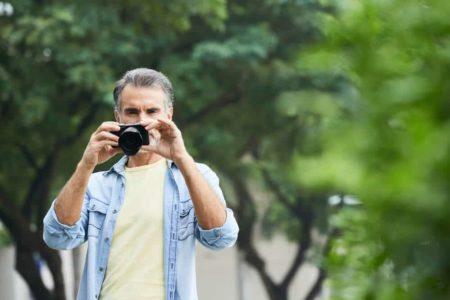 senior man using a camera outdoors