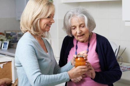 senior getting help opening a jar