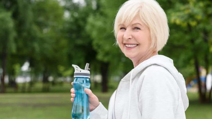 senior woman smiling and holding a water bottle