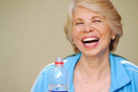 smiling senior opening a bottle