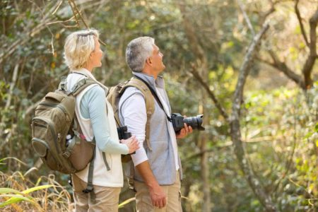 senior couple in woods watching for birds