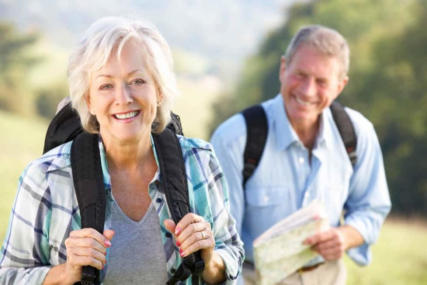 senior couple with backpacks on a hike