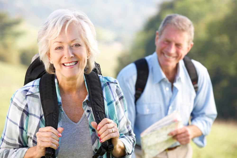 senior couple with backpacks on a hike