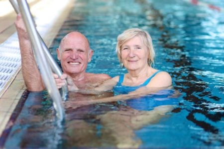 senior couple swimming in a large indoor pool