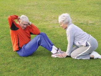 strong senior couple doing sit ups in the park