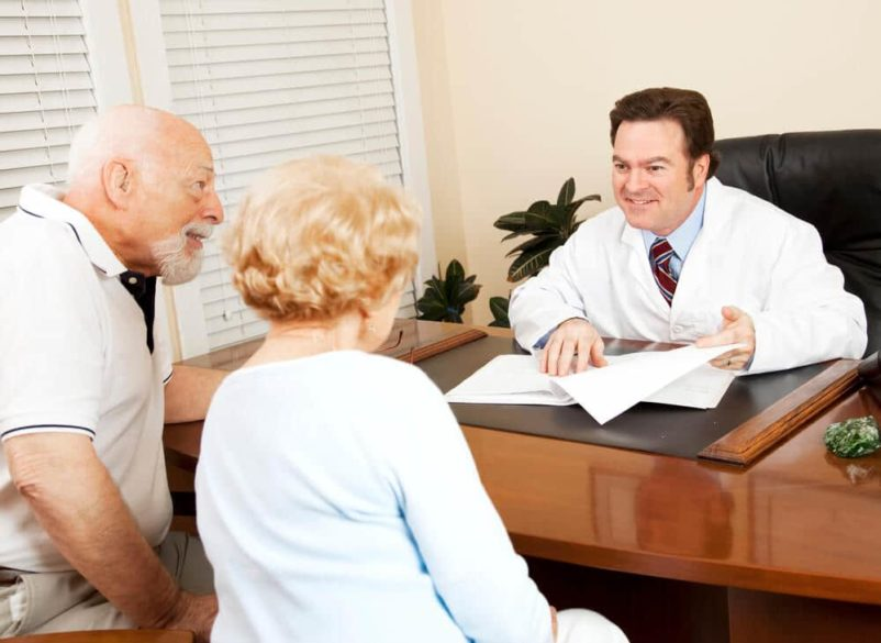 senior couple consulting with doctor about their hearing loss