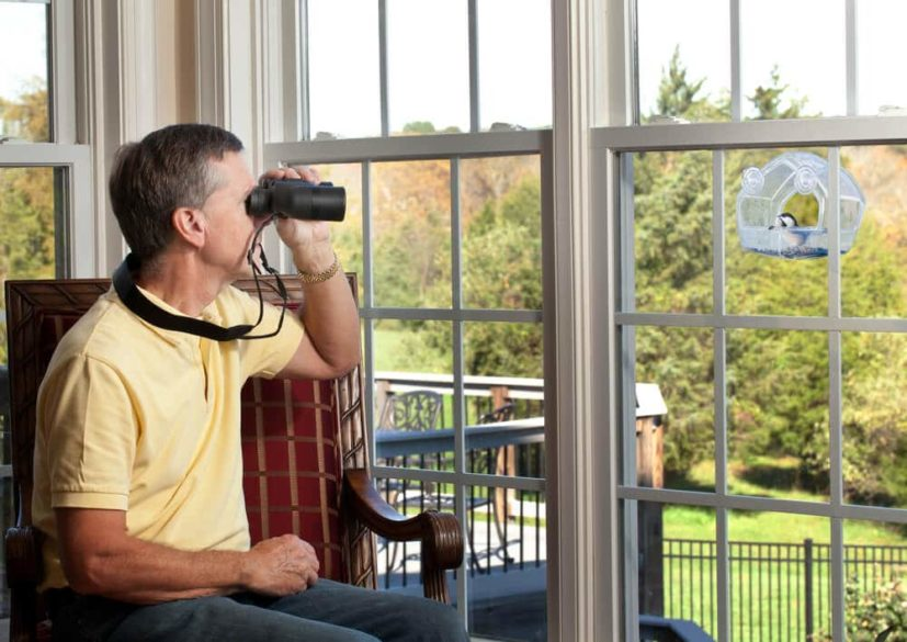 senior man with mobility issues birdwatching through the window