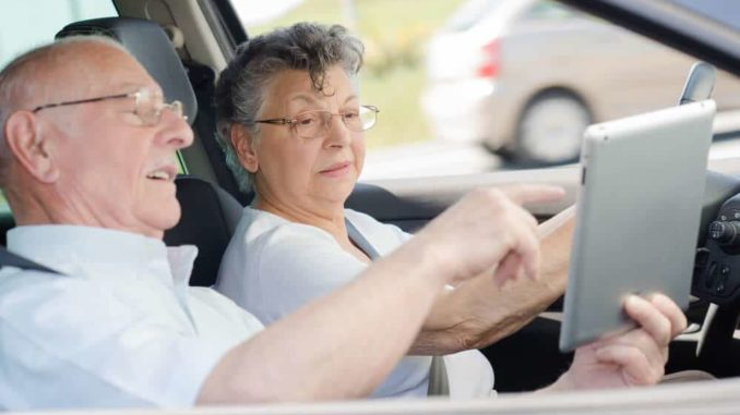 senior couple in car leaving for a day trip